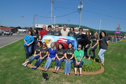 Employees of The Community State Bank pose for a picture with their new Patriotic Bull at their main location in Poteau.