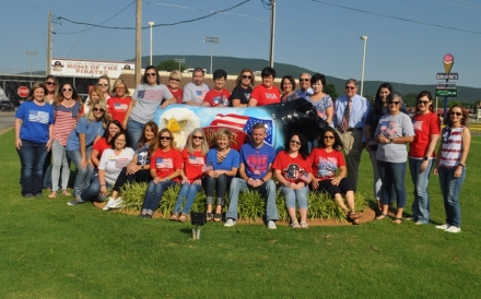 Employees from the Community State Bank decked out in their red, white and blue with their bull
