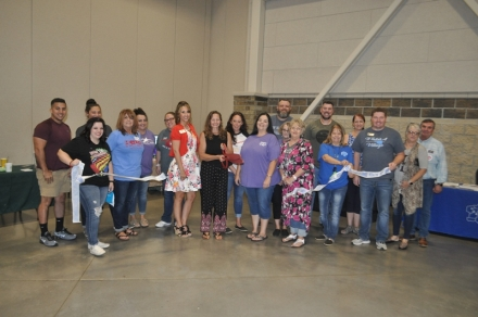 Members of the Poteau Chamber and friends join Jenny Carpenter for her Ribbon Cutting
