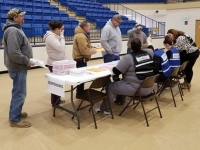 Volunteers practice processing forms at a POD in Pryor.