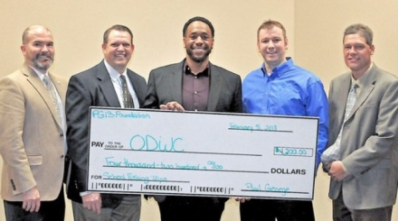 Receiving a $4,200 donation for the Oklahoma Fishing in the Schools Program from Myles Williams (center) of the Paul George Foundation are J.D. Strong, Wildlife Department director; Colin Berg, Education Section supervisor; Daniel Griffith, OKFITS coordinator; and Nels Rodefeld, Information and Education chief.