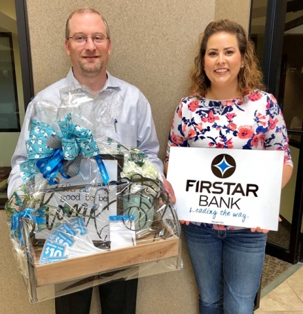 Marley Abell, left, holds the Firstar Bank basket donation next to CASC's Jaime Henson.