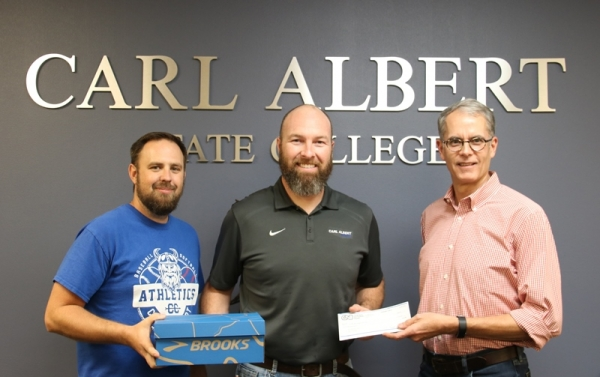 Josh Wiersig, left, stands with Head Coach Aaron Emberton, center, and Ron Hall to present CASC with donation items.