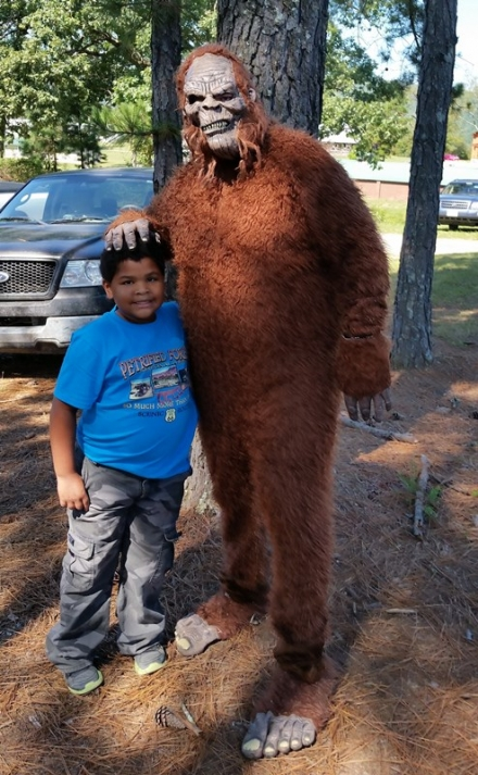 A festival Bigfoot greets a small visitor.